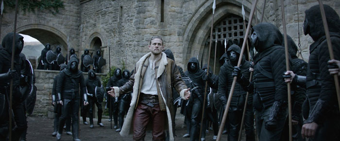 Charlie Hunnam as King Arthur. Wearing a football manager's sheepskin coat...