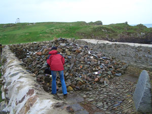 Putting a stone on the Pilgrimage Cairn at Isle of Whithorn